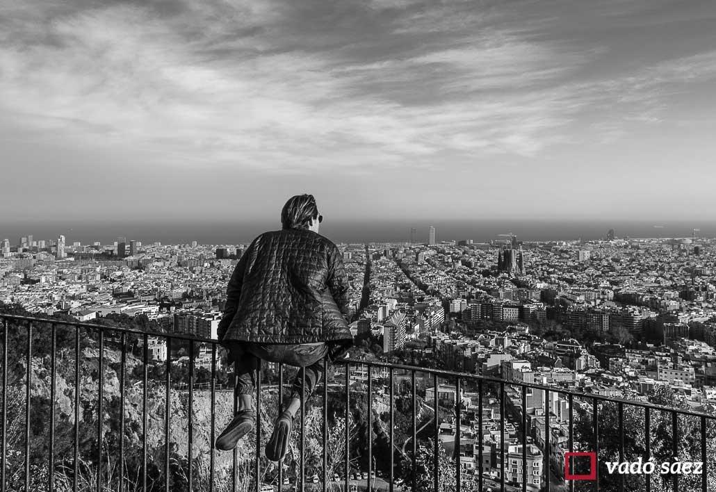 Noi observant la ciutat de Barcelona des de l'antiaeri del Parc del Guinardó