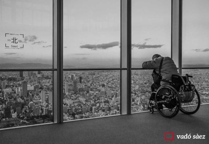 Home amb cadira de rodes contemplant la ciutat d'Osaka des d'observatori d'Abeno Harukas
