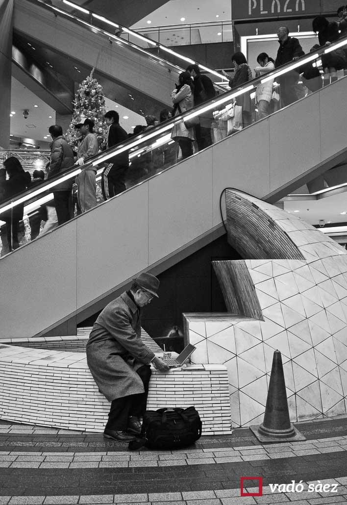 Home treballant amb el seu ordinador en centre comercial d'Ikebukuro