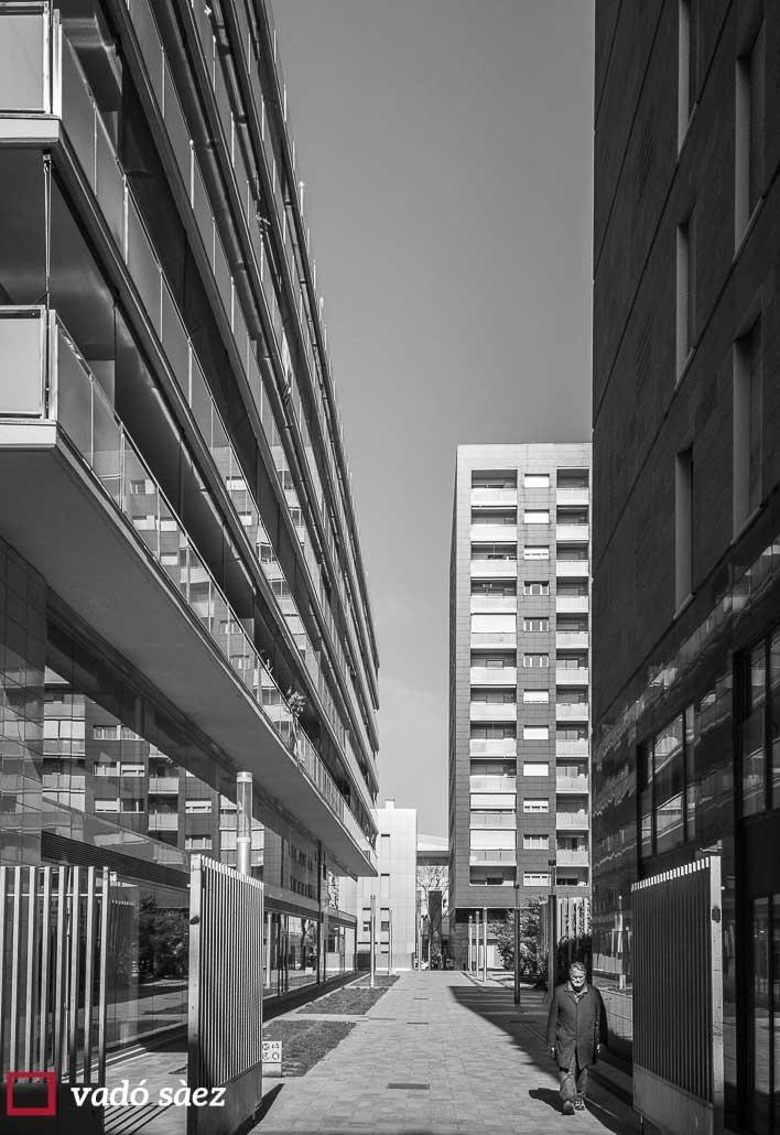 Home caminant per carreró envoltat d'edificis a l'Eixample de Barcelona