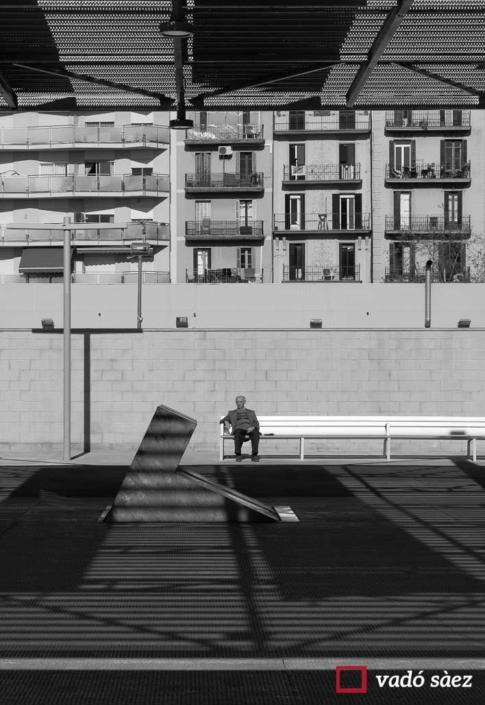 Home assegut en un banc al Parc Joan Miró a Barcelona