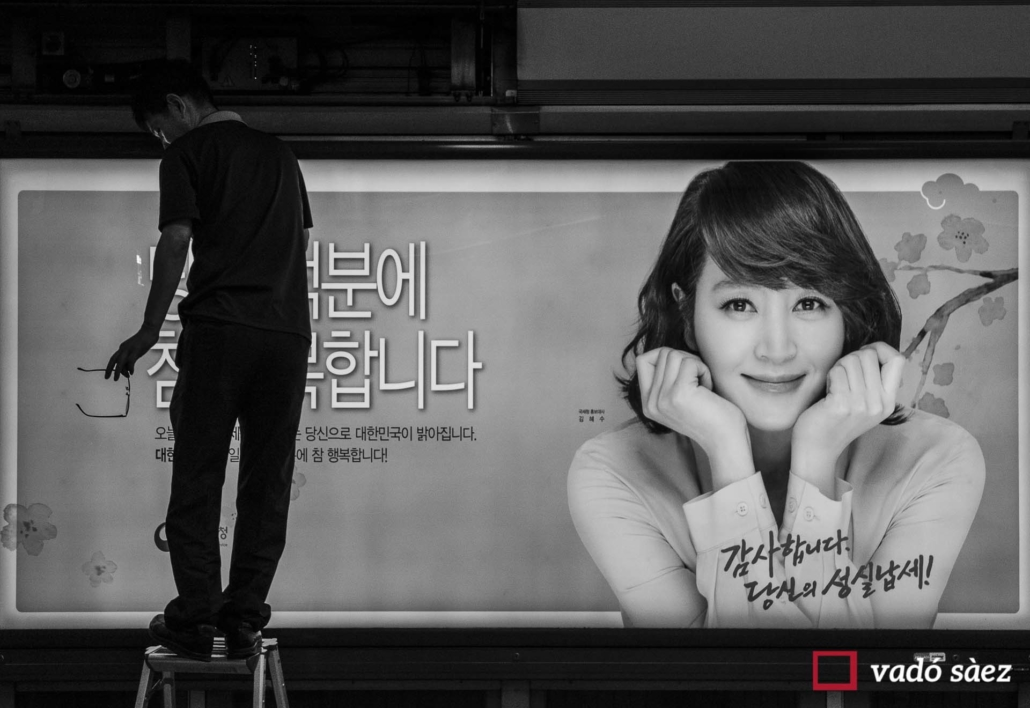 Home arreglant rètol publicitari al metro de Seül