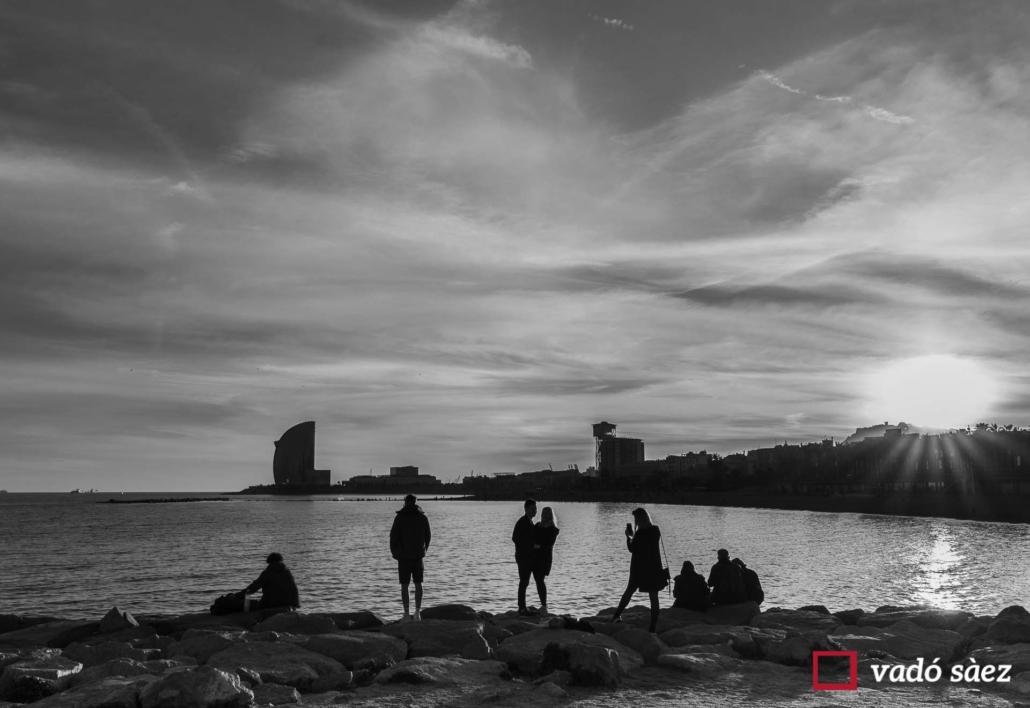Silueta d'un grup de persones que contemplen la posta de sol a la Barceloneta