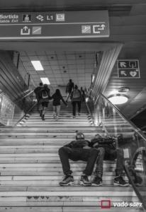 Nois dormint a les escales de l'estació de tren a plaça Catalunya de Barcelona
