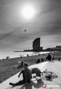 Noi amb bicicleta contemplant el mar a la platja de la Barceloneta