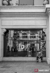 Home trist assegut a la porta d'un comerç al Portal de l'Àngel a Barcelona