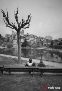 Parella asseguda vora del riu Llobregat contemplant el poble de Gironella